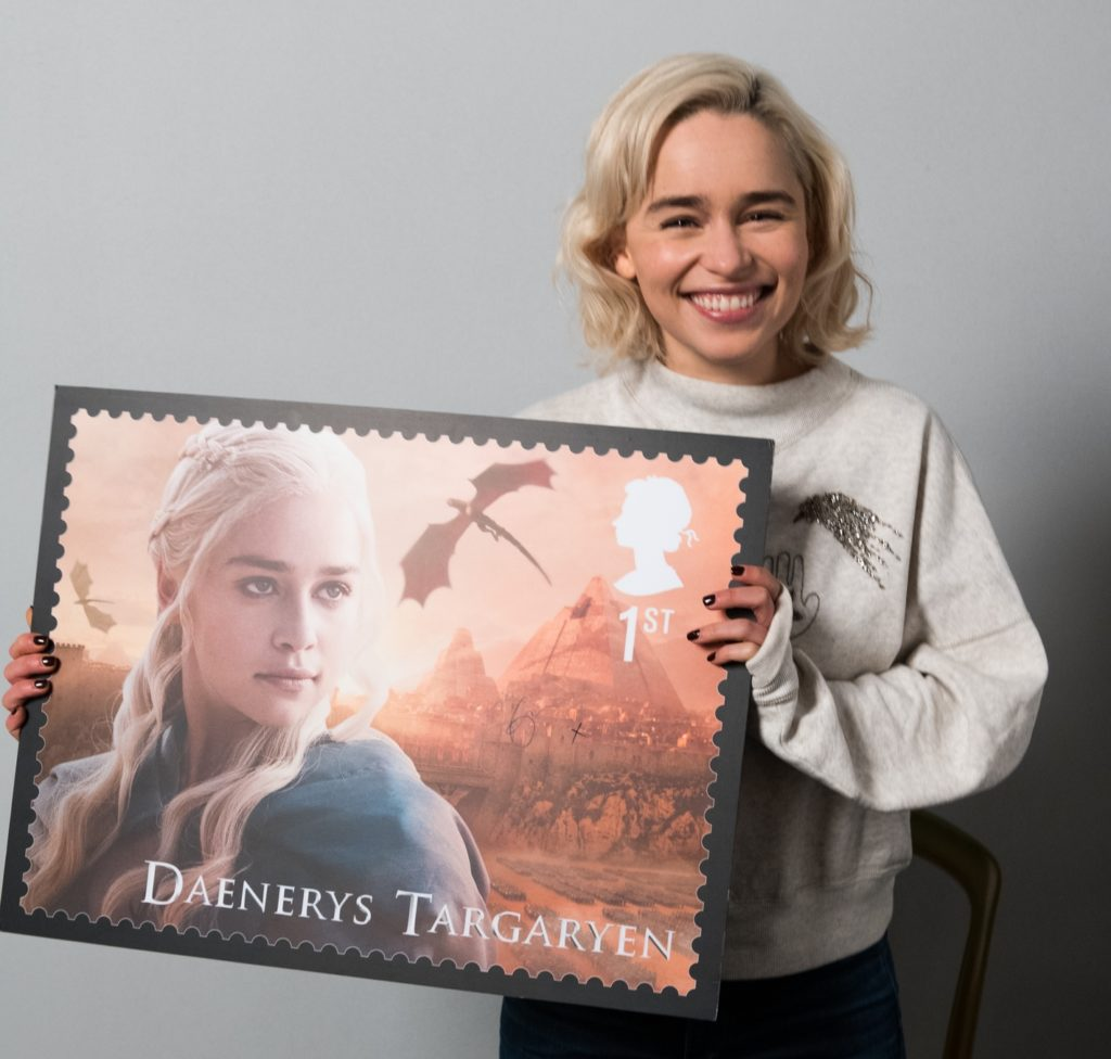 Emilia Clarke holding a print of the UK Mail postage stamp featuring Daenerys Targaryen in 2018.