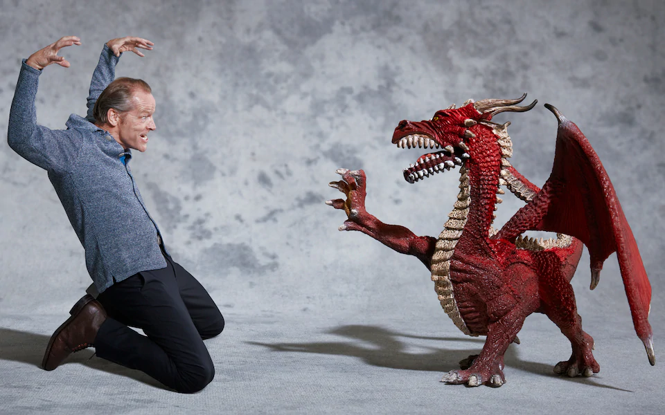 Iain Glen and an anatomically incorrect four-legged Drogon. Photo by Franck Allais for The Telegraph