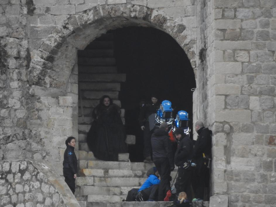 Jon Snow walks down the stairs of the tower, to the city walls