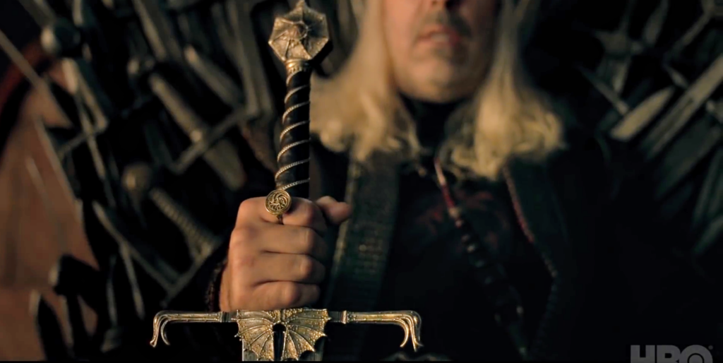 Paddy Considine's Viserys I Targaryen, sitting on the Iron Throne, grasps his sword as he grimaces;